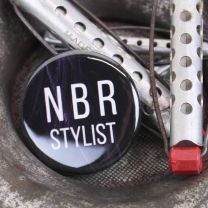 Close up of NBR Stylist button, with vintage hair rollers